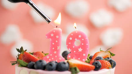 Birthday cake number 19, pink candle on beautiful cake with berries and lighter with fire against background of white clouds and pink sky. Close-up
