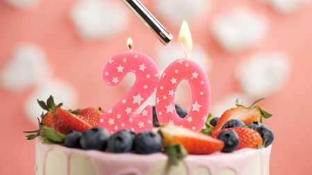 Birthday cake number 20, pink candle on beautiful cake with berries and lighter with fire against background of white clouds and pink sky. Close-up