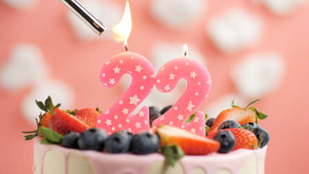 Birthday cake number 22, pink candle on beautiful cake with berries and lighter with fire against background of white clouds and pink sky. Close-up