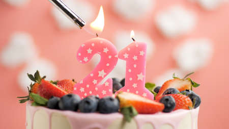 Birthday cake number 21, pink candle on beautiful cake with berries and lighter with fire against background of white clouds and pink sky. Close-up