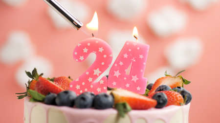 Birthday cake number 24, pink candle on beautiful cake with berries and lighter with fire against background of white clouds and pink sky. Close-up Imagens