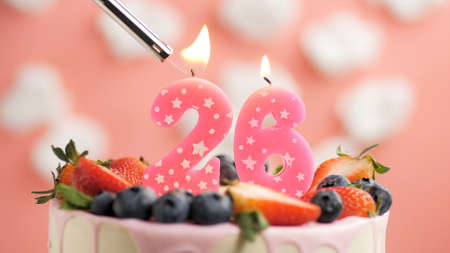 Birthday cake number 26, pink candle on beautiful cake with berries and lighter with fire against background of white clouds and pink sky. Close-up