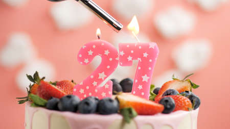 Birthday cake number 27, pink candle on beautiful cake with berries and lighter with fire against background of white clouds and pink sky. Close-up