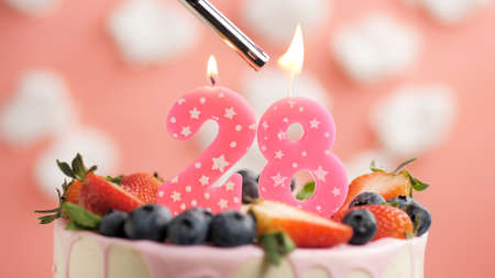 Birthday cake number 28, pink candle on beautiful cake with berries and lighter with fire against background of white clouds and pink sky. Close-up