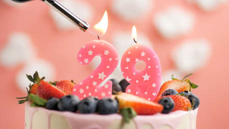 Birthday cake number 29, pink candle on beautiful cake with berries and lighter with fire against background of white clouds and pink sky. Close-up