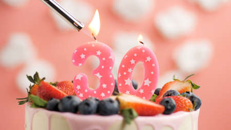 Birthday cake number 30, pink candle on beautiful cake with berries and lighter with fire against background of white clouds and pink sky. Close-up Imagens
