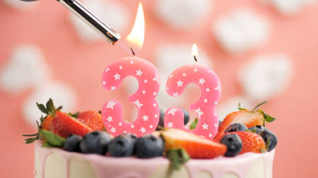 Birthday cake number 33, pink candle on beautiful cake with berries and lighter with fire against background of white clouds and pink sky. Close-up Imagens