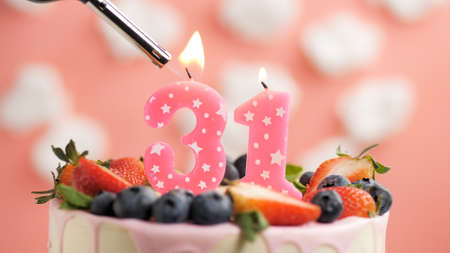 Birthday cake number 31, pink candle on beautiful cake with berries and lighter with fire against background of white clouds and pink sky. Close-up