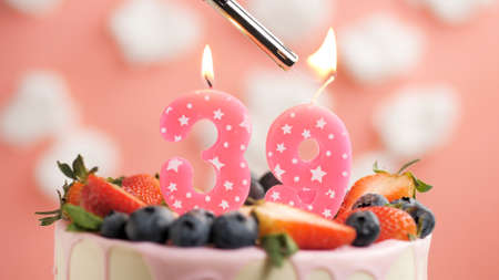 Birthday cake number 39, pink candle on beautiful cake with berries and lighter with fire against background of white clouds and pink sky. Close-up