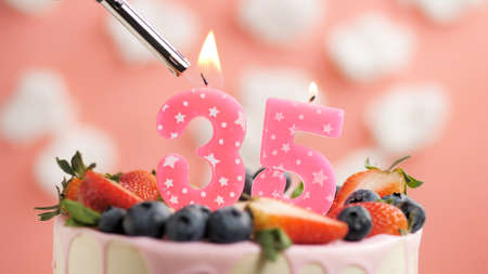 Birthday cake number 35, pink candle on beautiful cake with berries and lighter with fire against background of white clouds and pink sky. Close-up