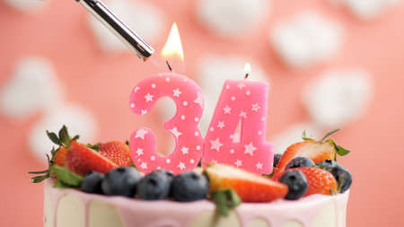 Birthday cake number 34, pink candle on beautiful cake with berries and lighter with fire against background of white clouds and pink sky. Close-up Imagens
