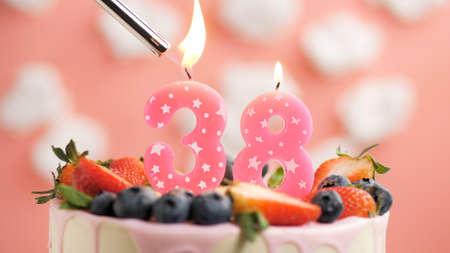 Birthday cake number 38, pink candle on beautiful cake with berries and lighter with fire against background of white clouds and pink sky. Close-up