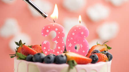 Birthday cake number 36, pink candle on beautiful cake with berries and lighter with fire against background of white clouds and pink sky. Close-up