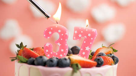 Birthday cake number 37, pink candle on beautiful cake with berries and lighter with fire against background of white clouds and pink sky. Close-up Imagens