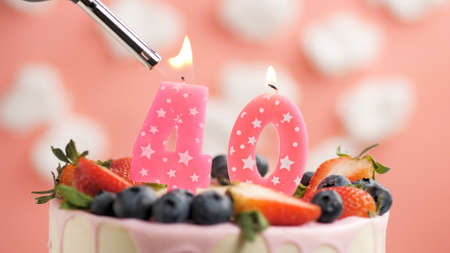 Birthday cake number 40, pink candle on beautiful cake with berries and lighter with fire against background of white clouds and pink sky. Close-up Imagens