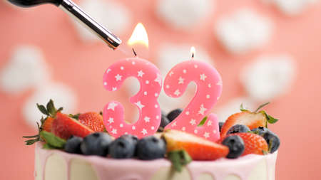 Birthday cake number 32, pink candle on beautiful cake with berries and lighter with fire against background of white clouds and pink sky. Close-up