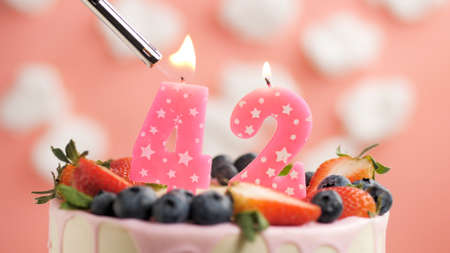 Birthday cake number 42, pink candle on beautiful cake with berries and lighter with fire against background of white clouds and pink sky. Close-up
