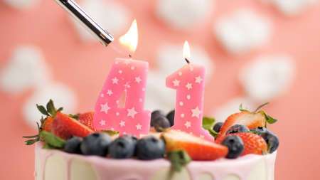 Birthday cake number 41, pink candle on beautiful cake with berries and lighter with fire against background of white clouds and pink sky. Close-up Imagens