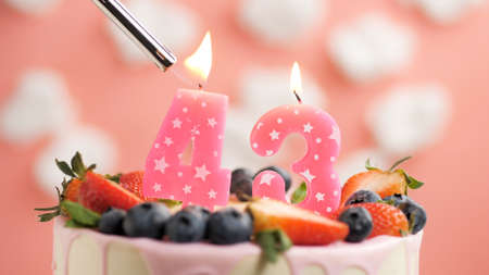 Birthday cake number 43, pink candle on beautiful cake with berries and lighter with fire against background of white clouds and pink sky. Close-up
