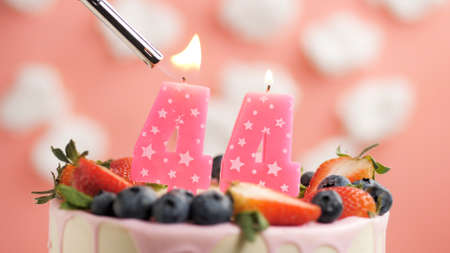 Birthday cake number 44, pink candle on beautiful cake with berries and lighter with fire against background of white clouds and pink sky. Close-up Imagens