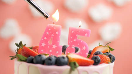 Birthday cake number 45, pink candle on beautiful cake with berries and lighter with fire against background of white clouds and pink sky. Close-up Imagens