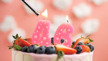 Birthday cake number 46, pink candle on beautiful cake with berries and lighter with fire against background of white clouds and pink sky. Close-up