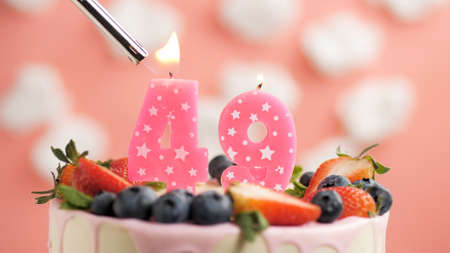 Birthday cake number 49, pink candle on beautiful cake with berries and lighter with fire against background of white clouds and pink sky. Close-up Imagens