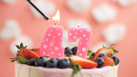 Birthday cake number 47, pink candle on beautiful cake with berries and lighter with fire against background of white clouds and pink sky. Close-up