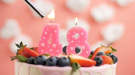 Birthday cake number 48, pink candle on beautiful cake with berries and lighter with fire against background of white clouds and pink sky. Close-up