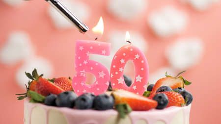 Birthday cake number 50, pink candle on beautiful cake with berries and lighter with fire against background of white clouds and pink sky. Close-up