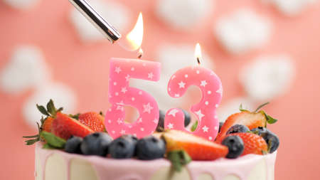Birthday cake number 53, pink candle on beautiful cake with berries and lighter with fire against background of white clouds and pink sky. Close-up Imagens