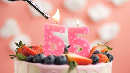 Birthday cake number 55, pink candle on beautiful cake with berries and lighter with fire against background of white clouds and pink sky. Close-up