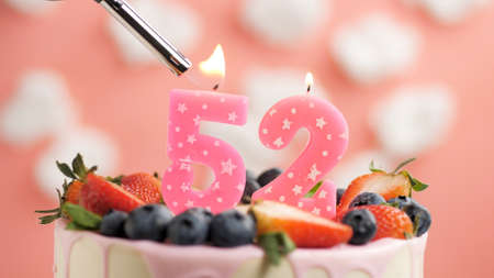 Birthday cake number 52, pink candle on beautiful cake with berries and lighter with fire against background of white clouds and pink sky. Close-up