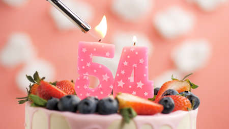 Birthday cake number 54, pink candle on beautiful cake with berries and lighter with fire against background of white clouds and pink sky. Close-up Imagens