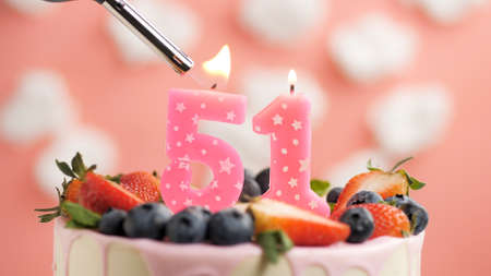 Birthday cake number 51, pink candle on beautiful cake with berries and lighter with fire against background of white clouds and pink sky. Close-up