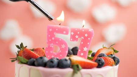Birthday cake number 57, pink candle on beautiful cake with berries and lighter with fire against background of white clouds and pink sky. Close-up Imagens