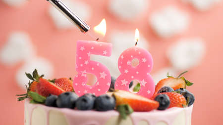 Birthday cake number 58, pink candle on beautiful cake with berries and lighter with fire against background of white clouds and pink sky. Close-up
