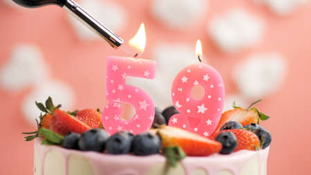 Birthday cake number 59, pink candle on beautiful cake with berries and lighter with fire against background of white clouds and pink sky. Close-up