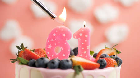 Birthday cake number 61, pink candle on beautiful cake with berries and lighter with fire against background of white clouds and pink sky. Close-up