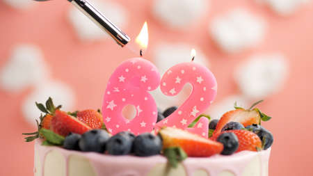 Birthday cake number 62, pink candle on beautiful cake with berries and lighter with fire against background of white clouds and pink sky. Close-up