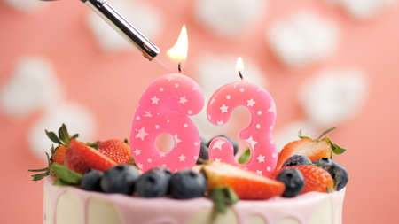 Birthday cake number 63, pink candle on beautiful cake with berries and lighter with fire against background of white clouds and pink sky. Close-up