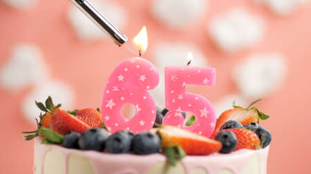 Birthday cake number 65, pink candle on beautiful cake with berries and lighter with fire against background of white clouds and pink sky. Close-up