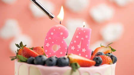Birthday cake number 64, pink candle on beautiful cake with berries and lighter with fire against background of white clouds and pink sky. Close-up Imagens