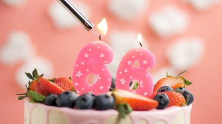 Birthday cake number 66, pink candle on beautiful cake with berries and lighter with fire against background of white clouds and pink sky. Close-up Imagens