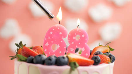 Birthday cake number 68, pink candle on beautiful cake with berries and lighter with fire against background of white clouds and pink sky. Close-up