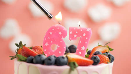 Birthday cake number 67, pink candle on beautiful cake with berries and lighter with fire against background of white clouds and pink sky. Close-up