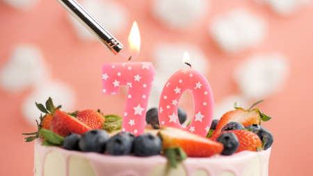 Birthday cake number 70, pink candle on beautiful cake with berries and lighter with fire against background of white clouds and pink sky. Close-up