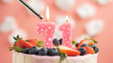 Birthday cake number 71, pink candle on beautiful cake with berries and lighter with fire against background of white clouds and pink sky. Close-up