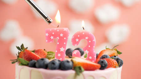 Birthday cake number 73, pink candle on beautiful cake with berries and lighter with fire against background of white clouds and pink sky. Close-up Imagens