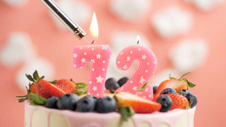 Birthday cake number 72, pink candle on beautiful cake with berries and lighter with fire against background of white clouds and pink sky. Close-up